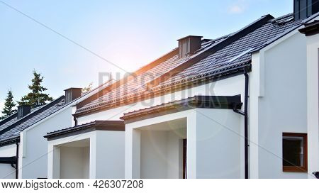 New Single Family House In A New Development Area. Residential Home With Modern Facade. Rays Of The