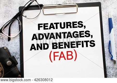 Business Acronym Fab - Feature Advantage Benefits. Text On A Sheet Of Notepad On A Black Envelope On