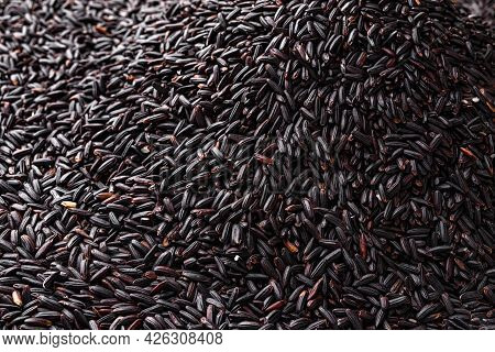 Pile Of Raw Black Rice As A Background. Texture Of Uncooked Dark Rice Heap. Unpolished Organic Black