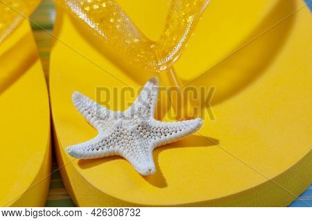 Yellow Rubber Beach Flip Flops And Starfish On A Blue Wooden Background, Place Under The Text