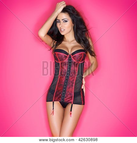Beautiful busty woman in a sexy corset with long brunette hair posing against a pink studio background
