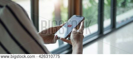 Thailand - Jan 20, 2021 :woman Holding Iphone Xs With Video Service Youtube On The Screen. Iphone Wa