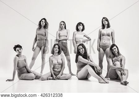 Women Without Makeup In Beige Clothes. Black And White Photo With A Group Of Girls On A Light Backgr