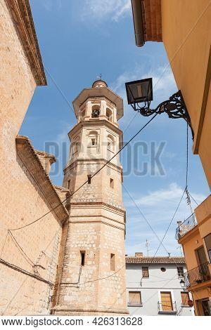 Alcalali Church Spire Rising Through Narrow Typically Historic Mediterranean Village Street, Spain.