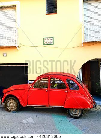 Alicante Spain - February 2015; Red Citroen Cv2 Small Red Car Parked Outside Yellow Building Under S