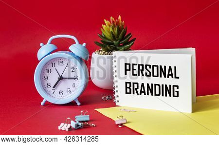 Personal Branding Text Written On Notepad. On A Red And Yellow Background Alarm Clock, Cactus And Pa