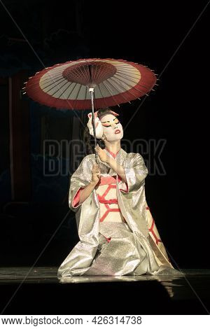 Japanese Woman In Traditional Kimono With Umbrella Sitting On The Knees In Darkness, Lighten By The