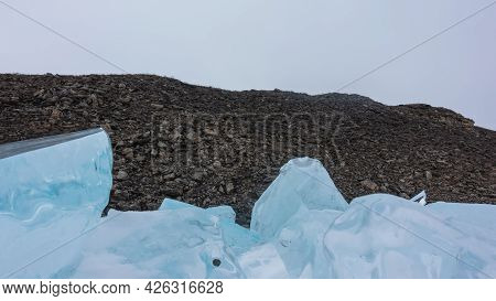 A Block Of Blue Ice Hummocks Against The Background Of A Granite Rock Devoid Of Vegetation. Shiny Ic