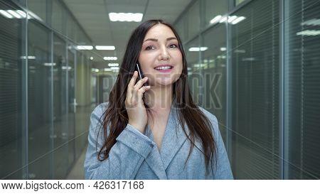 Brunette Businesswoman In Grey Jacket Talks On Black Smartphone Standing In Building Lounge With Gla