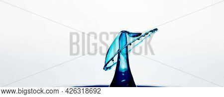 Splash and crown on rippled blue liquid or water surface . Water splash with a crown and reflection
