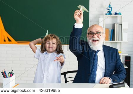 Happy Kid In School. Old Senior Teacher And Pupil Hold Paper Airplane. Education, Teachering, Elemen