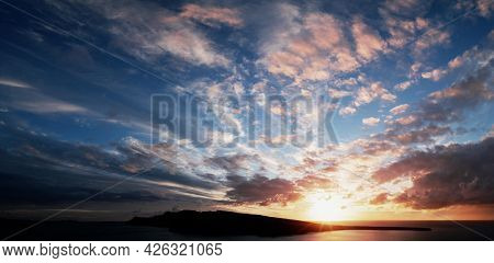 The sun sets over the sea horizon. Sunset on the sea against the backdrop of the island