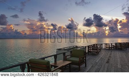 Evening In The Maldives. There Are Tables And Chairs On A Wooden Platform Above The Ocean. In The Bl