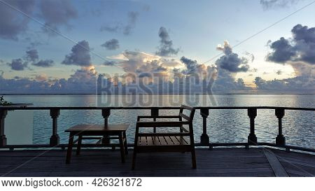 Quiet Maldivian Evening. There Are Pink And Lilac Clouds In The Blue Sky. On A Wooden Platform Above