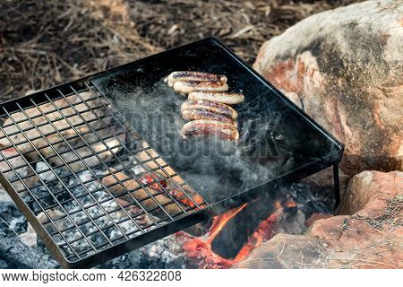 Camp Cooking. Grilling Sausages On A Cast Iron Plate Over The Camp Fire. Camping Lifesyle