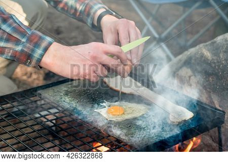Breakfast Camp Cooking. Grilling Crispy Bacon And Eggs On A Cast Iron Plate Over The Camp Fire. Camp