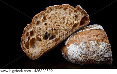 A Loaf Of Rye Bread Cut In Half On A Black Background.