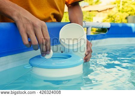 Hand Holding White Chlorine Tablets Over Swimming Pool Skimmer. Chlorination Of Water In Pool For Di
