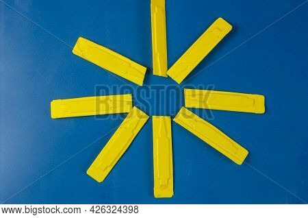 Geometric Shape Of  Dog Flea And Tick Drops Against Blue. Yellow Plastic Container With Veterinary A
