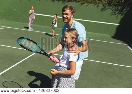 Happy caucasian couple with daughter and son outdoors, playing tennis on tennis court. family enjoying healthy free time activities together.