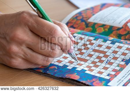 A Womans Hand With A Pen Writes Solutions To A Crossword Puzzle, Closeup, Mind Training Concept