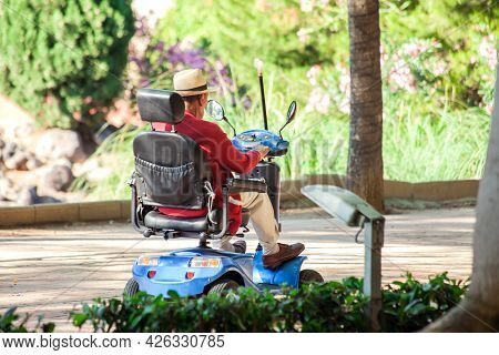 Senior Man Using Electric Wheelchair In The Park. Lifestyle And Independence Of Disabled People