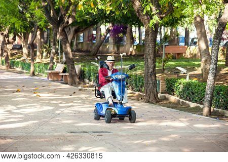 Torrevieja, Spain, 24.05.2021, Disabled Senior Man Using Electric Wheelchair In The Park. Lifestyle