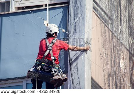High Altitude Worker At Rope. Specially Equipped Worker Performs Height Work