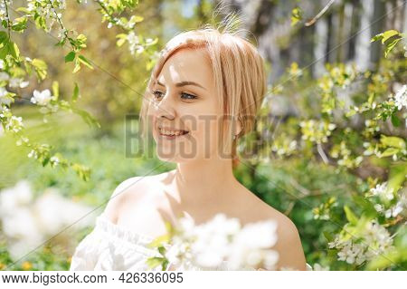 Young Beautiful Happy Smiling Blonde Woman Posing In Blooming Spring Garden With White Flowers. Bloo