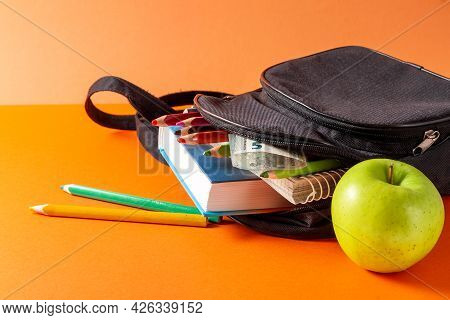 Open School Backpack On An Orange Background. Books, A Notebook And Pencils Are Sticking Out Of An O