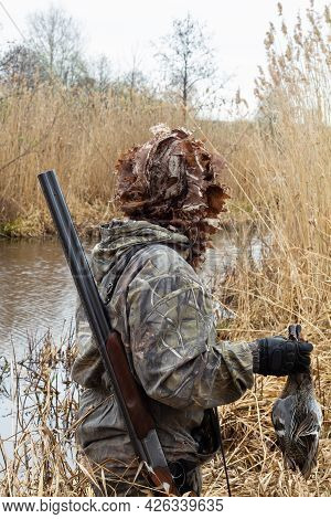 The Hunter Is Standing On The Shore Of A Lake That Is Overgrown With Reeds. He Holds In His Hands Hi