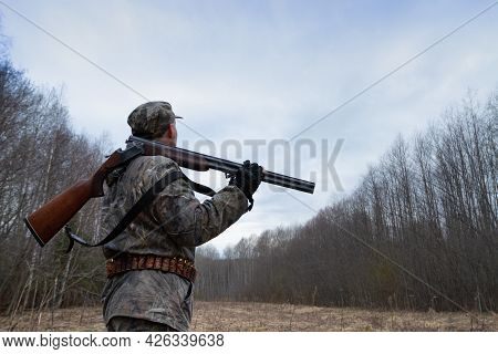 A Hunter With An Unloaded Shotgun On His Shoulder Stands In A Forest Clearing At Dusk. He Looks At T