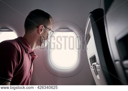 Passenger With Protective Face Mask In Airplane Looking Through Window. Themes Traveling In New Norm
