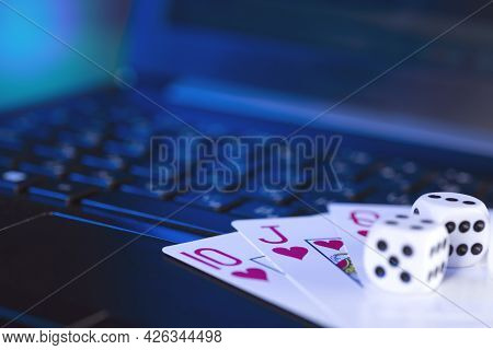 Online Gaming Platform, Casino And Gambling Business. Cards And Dice On Laptop Keyboard, Toned In Bl