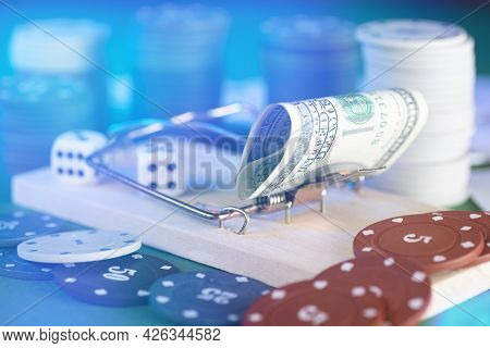 Banknote And Mousetrap, Game Trap, Against The Background Of Casino Chips And Dice