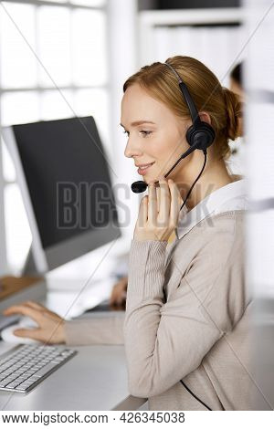 Friendly Businesswoman Talking By Headset While Sitting In Office. Call Center And Diverse People Gr