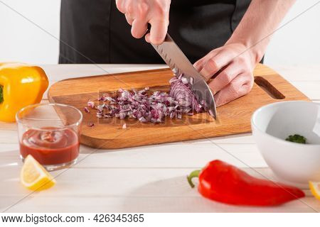 Close-up On Chefs Hands Cutting Onion With A Santoku Knife