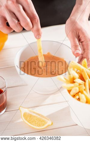 Close-up On A Hand Dipping French Fries Into Sauce Andalouse