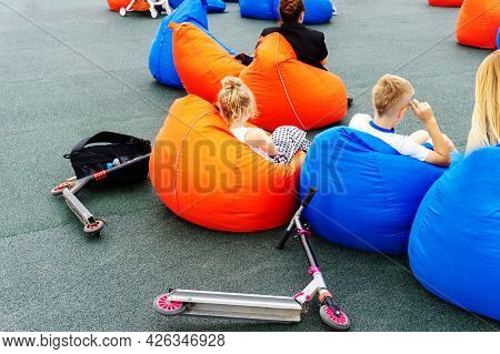 Children Relax On A Bob Bag In The Relaxation Area. Outdoor Sports Ground. Unrecognizable Person