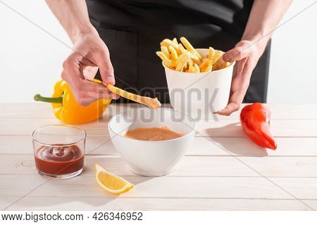 Man Dipping French Fries Into Homemade Sauce Andalouse