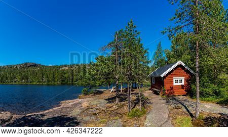 An Idyllic Wooden Red Cottage In Coastal Forest Landscape On The Baltic Sea In Northern Sweden