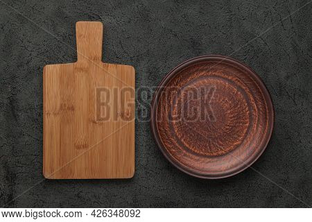 Brown Wooden Cutting Board, Empty Brown Clay Plate On Black Stone Table. Top View With Copy Space..