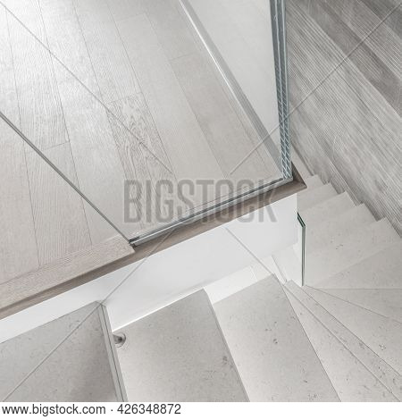 Modern Design And Innovative Material. Microcement Stairs With Glass Handrail. Stairs Viewed From Ab