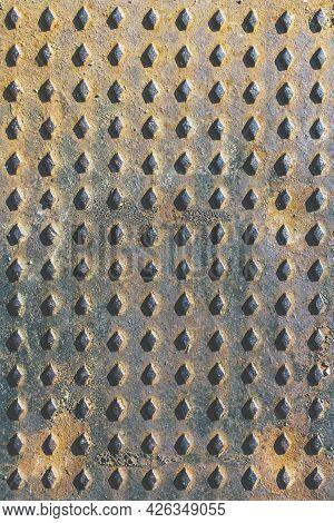 Rusty Sewer Manhole Cover. Geometric Pattern On The Cover Of The Sewer Manhole. Close-up View Of The