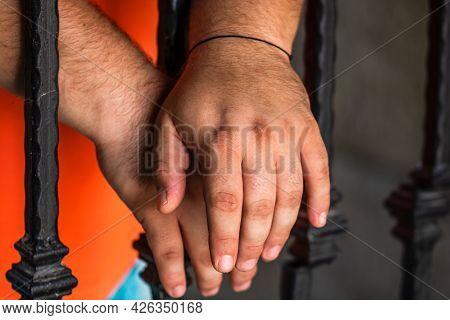 Prisoner Man Holding Hands On Jail Bars. Hands On Prison Bars.
