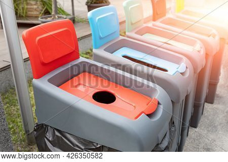Row Of Many Different Multicolored Plastic Waste Cans For Garbage Sorting And Recycling At City Stre
