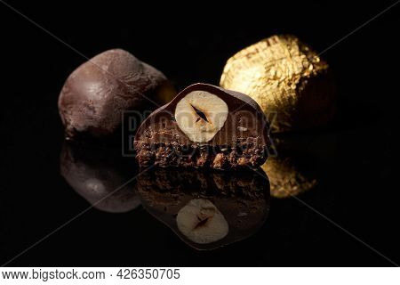 A Cut Chocolate Candy With A Nut And Two Whole Candies, One Of Which Is In A Golden Wrapper On A Bla