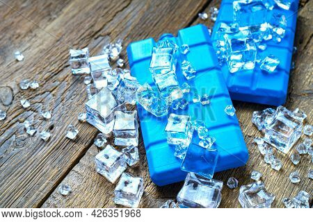 Blue Cold Accumulators Blocks In The Ice On A Wooden Background. Concept Of Summer Tourism.