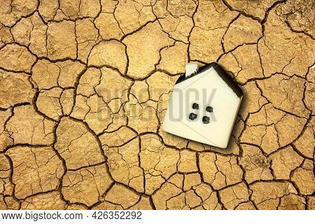 Global Warming And Climate Changing Concept With A Little Toy House On The Dried Soil.
