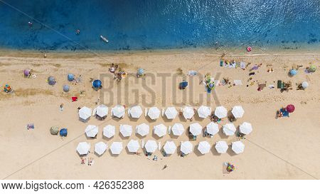 Aerial. Sandy Beach With Tourists By The Sea. Top View From Drone.